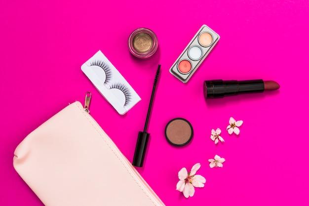 Fiore di primavera; ciglia; ombretto; rossetto; pennello mascara e fiore con sacchetto di trucco rosa su sfondo rosa
