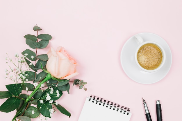 Fiore di rosa con caffè; blocco note a spirale e penna stilografica su sfondo rosa