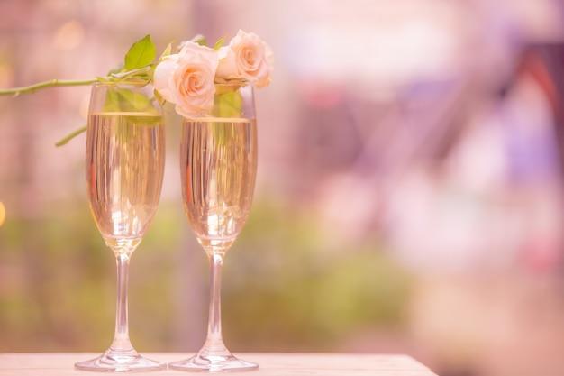 Fiore di rosa su vino di vetro con il bokeh della sfuocatura