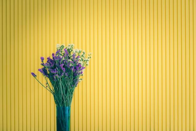 Fiore giallo e viola in vaso su sfondo giallo.