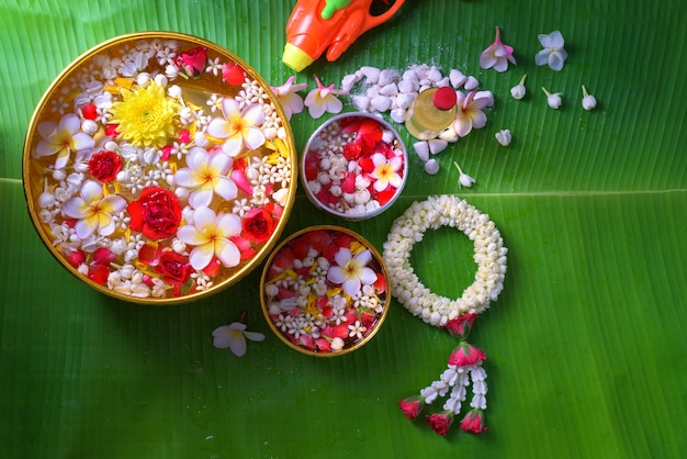 Fiore in acqua bocce e pistola a cannone su foglia di banana per songkran festival o thai n