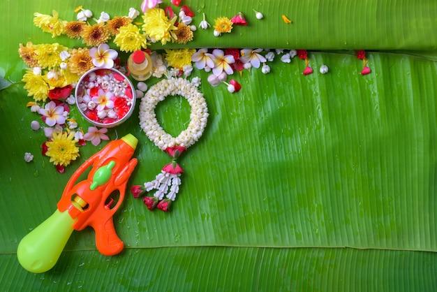 Fiore in acqua bocce e pistola a cannone su foglia di banana per songkran festival o thai nuovo anno