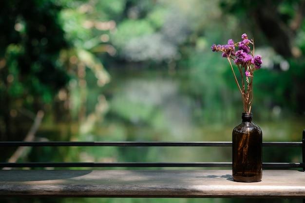 Fiore porpora in un posto della bottiglia sulla tavola di legno con il fondo blured del canale con lo ps della copia