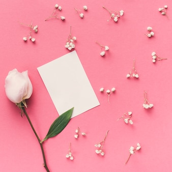 Fiore rosa con piccola carta sul tavolo