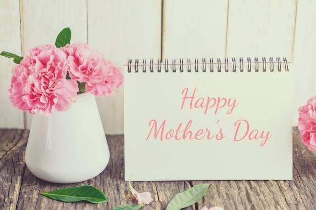 Fiore rosa del garofano con il testo felice di festa della mamma sul documento di carta bianco con il tono d'annata