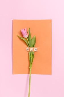 Fiore singolo tulipano rosa; carta arancione con blocco di testo mamma in legno su sfondo colorato