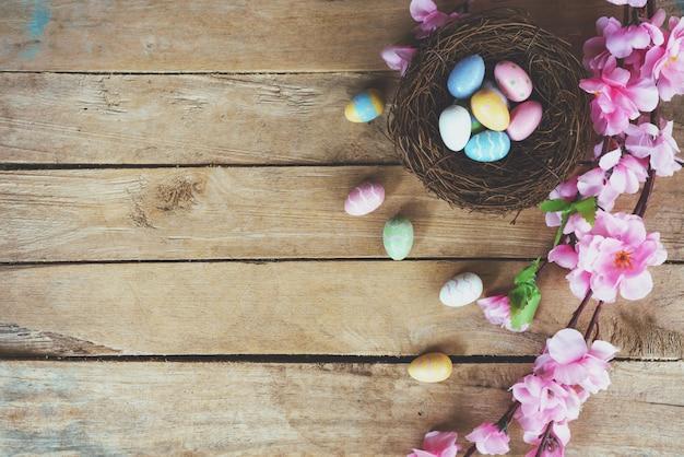 Fiori artificiali e uovo di pasqua del fiore di ciliegia in nido su fondo di legno d'annata con lo spazio della copia.