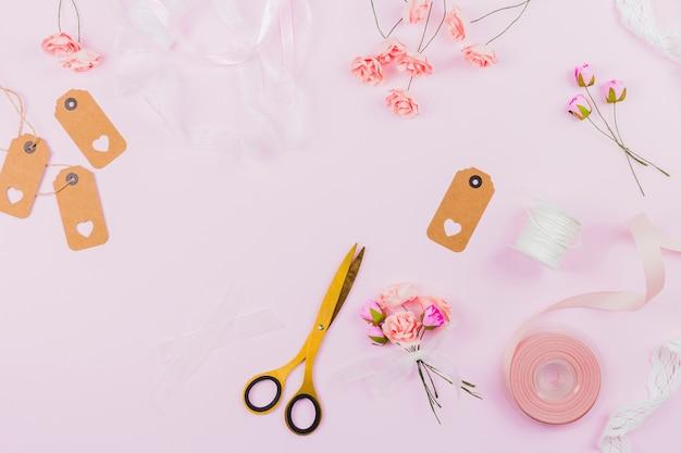 Fiori artificiali finti con nastro; etichetta e forbice su sfondo rosa