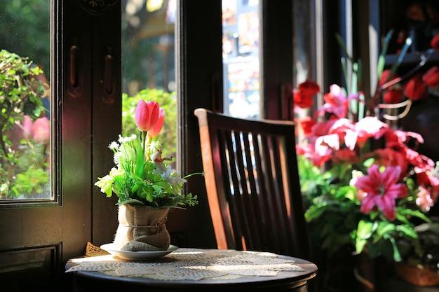 Fiori artificiali in vaso marrone sacco sul tavolo