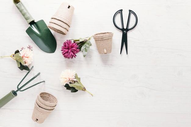 Fiori artificiali; pentola di torba e attrezzi da giardinaggio disposti in forma circolare con forbici sul tavolo bianco