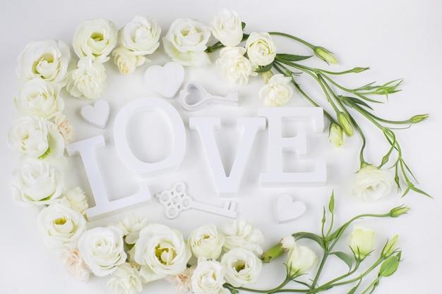 Fiori bianchi, chiavi decorative e la parola amore