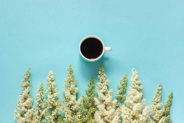 Fiori bianchi del ramoscello di fioritura di fila e della tazza di caffè sul fondo della carta blu