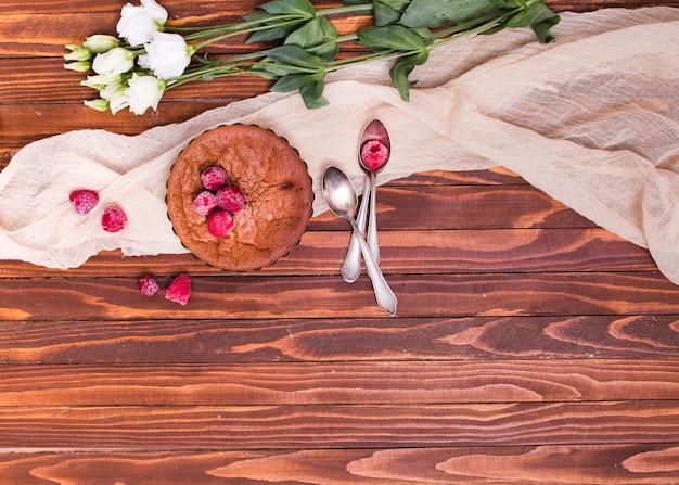 Fiori bianchi di eustoma; cotto al forno con condimenti di lamponi e cucchiai sul tessuto sopra la superficie di legno