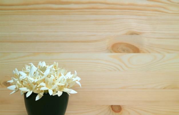 Fiori bianchi di millingtonia in vaso blu profondo su fondo di legno con lo spazio della copia