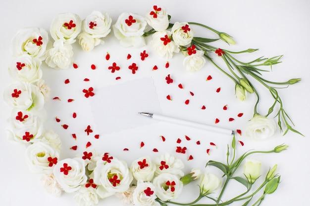 Fiori bianchi e fiori rossi e un foglio di carta