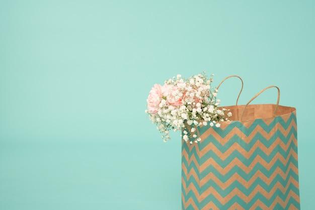 Fiori bianchi e rosa nel sacchetto della spesa isolato sul blu