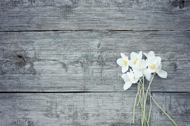 Fiori bianchi su fondo in legno vecchio. fiori del giardino sul fondo della tavola in legno.