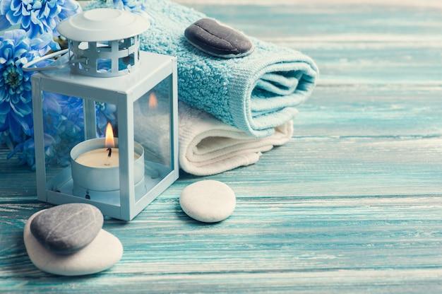 Fiori blu, ciottoli e lume di candela