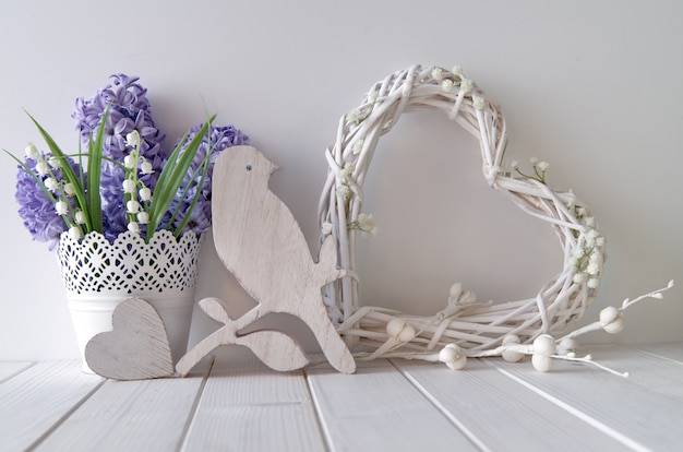 Fiori blu del giacinto e del mughetto, cuore di legno, uccello e un cuore bianco dell'acacia