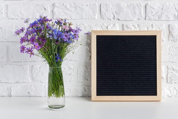 Fiori blu del mazzo in vaso e tabellone per le affissioni nero in bianco sulla tavola contro il muro di mattoni bianco.