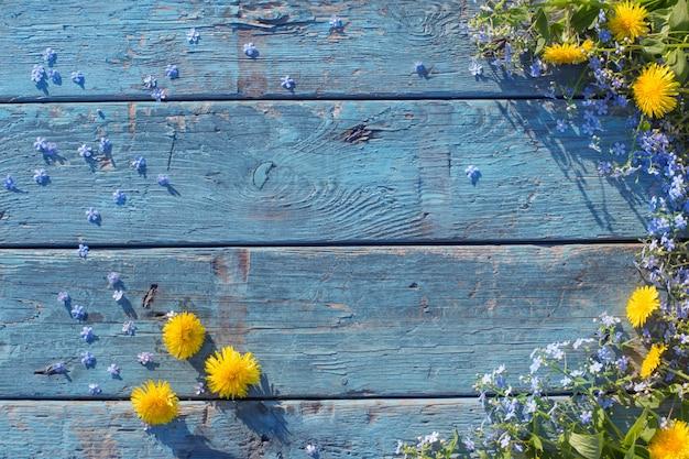 Fiori blu e gialli su vecchio legno