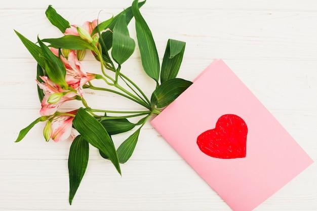 Fiori con biglietto di auguri con disegno di cuore