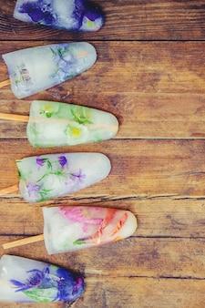 Fiori congelati in cubetti di ghiaccio e gelato su un bastone. messa a fuoco selettiva.