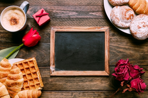 Fiori, cornice per foto, panetteria su piatti, confezione regalo e tazza di bevanda