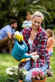 Fiori d'innaffiatura della donna su erba all'iarda