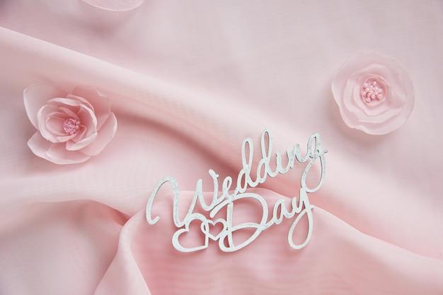 Fiori decorativi del tessuto, gioielli nuziali su chiffon rosa sul fondo del libro bianco