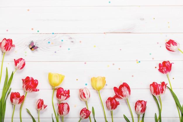 Fiori dei tulipani nella priorità bassa di legno.