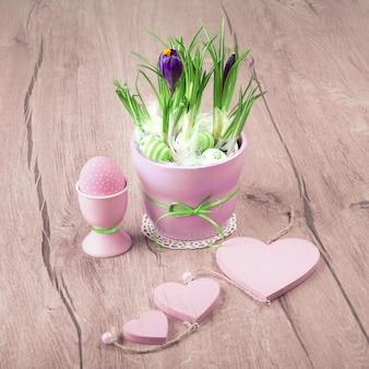 Fiori del croco e decorazioni rosa di pasqua su legno
