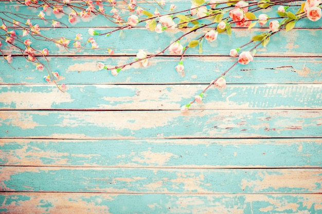 Fiori del fiore di ciliegia su fondo di legno d'annata, progettazione del confine