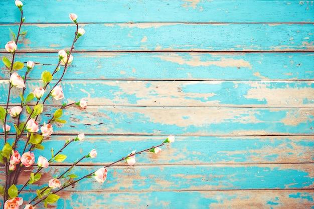 Fiori del fiore di ciliegia su fondo di legno d'annata, progettazione del confine.