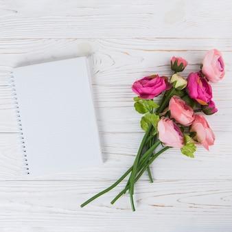 Fiori della rosa di rosa con il taccuino in bianco sulla tavola