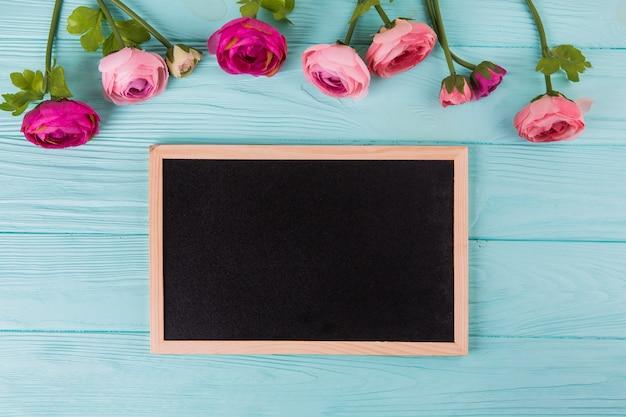 Fiori della rosa di rosa con la lavagna sulla tavola di legno