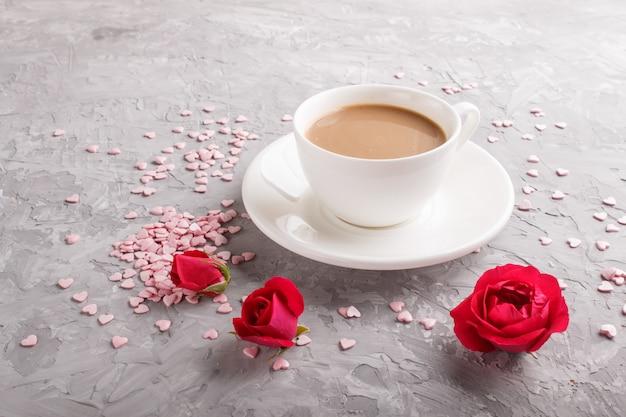 Fiori della rosa rossa e una tazza di caffè su calcestruzzo grigio