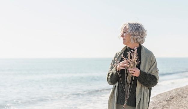 Fiori della tenuta della donna anziana del colpo medio