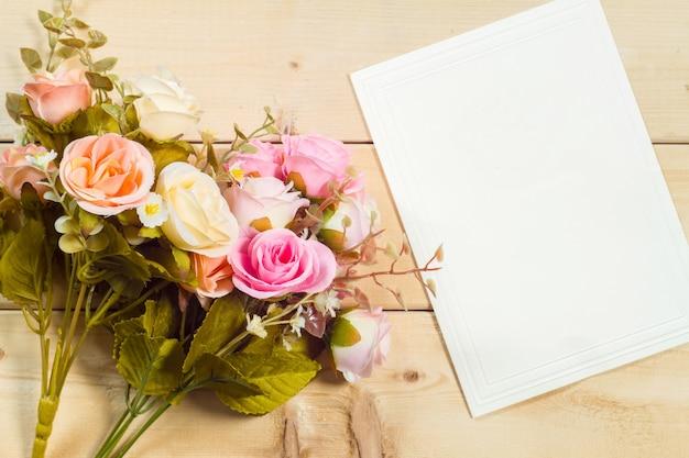 Fiori delle rose e pagina vuota su fondo di legno