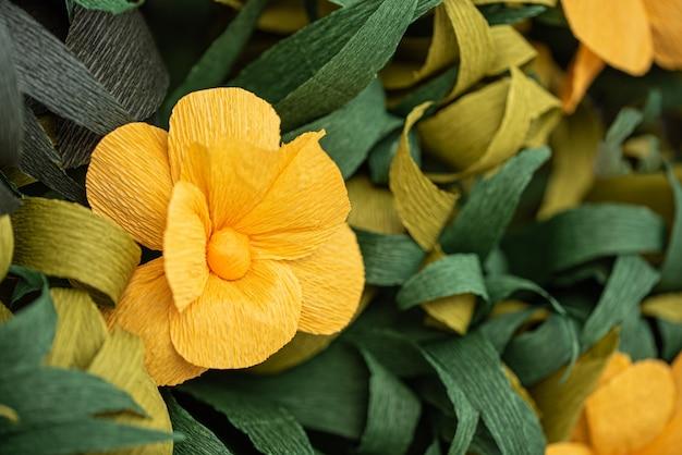 Fiori di carta gialli tra le foglie verdi