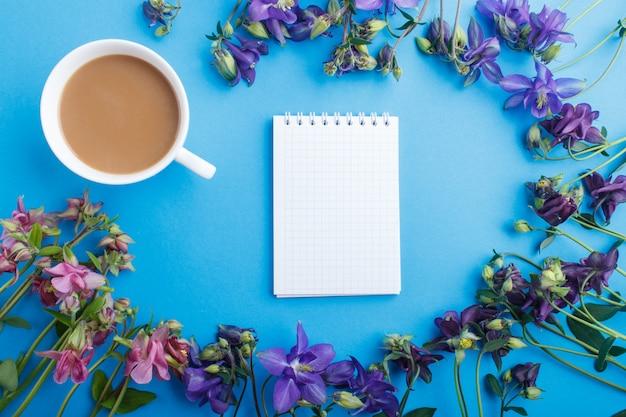 Fiori di colombina rosa e viola e una tazza di caffè con il taccuino sul blu pastello.