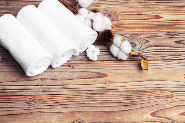 Fiori di cotone con asciugamano sul tavolo di legno