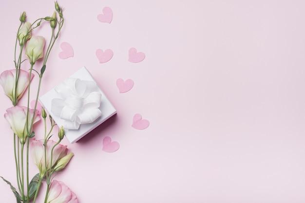 Fiori di eustoma con cuori rosa e scatola regalo bianca con nastro su sfondo colorato