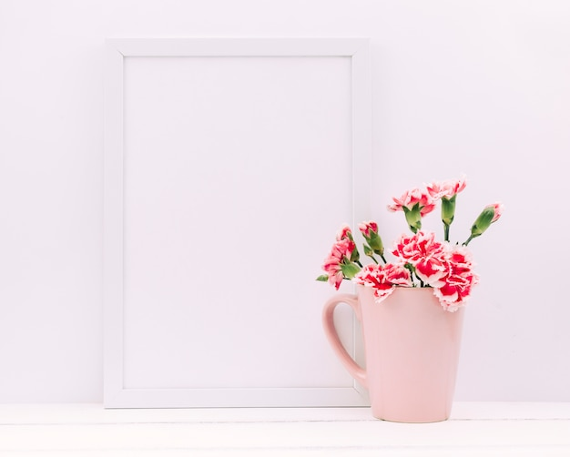 Fiori di garofano in vaso con cornice vuota sul tavolo