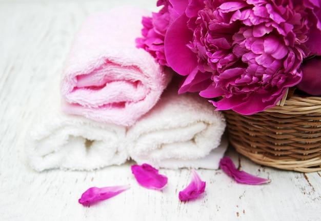 Fiori di peonia con asciugamani per massaggi
