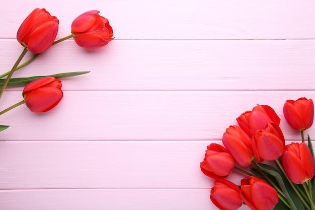 Fiori di primavera. mazzo di tulipani rossi su sfondo rosa.