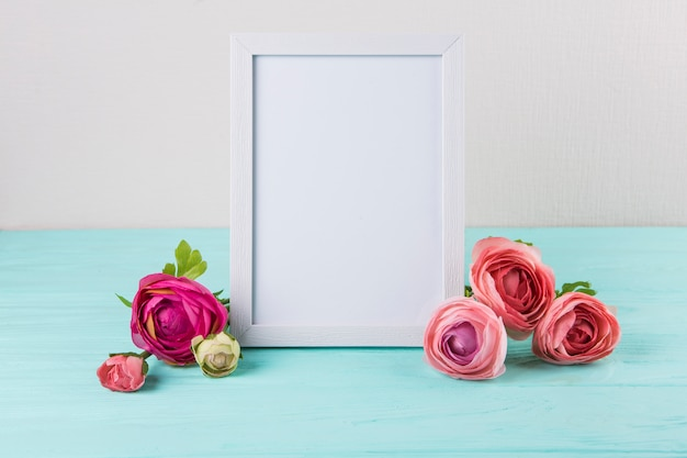 Fiori di rosa con cornice vuota sul tavolo