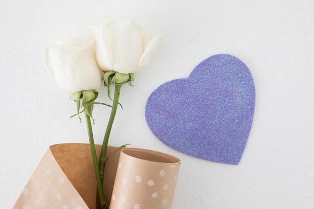 Fiori di rosa con cuore di carta sul tavolo