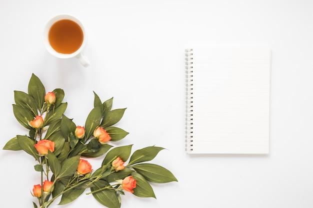 Fiori di rosa con notebook e tazza di tè