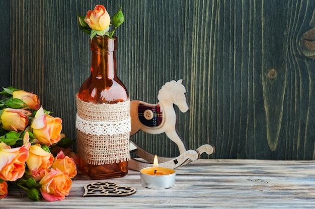 Fiori di rose arancioni freschi, cuore, bottiglia decorativa e candela accesa